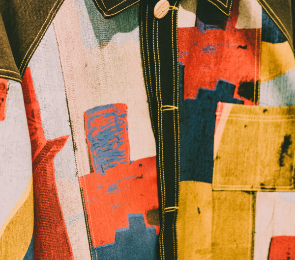 A jacket designed by Bethany Williams shown in a close up detail. The jacket is made using printed denim fabrics.
