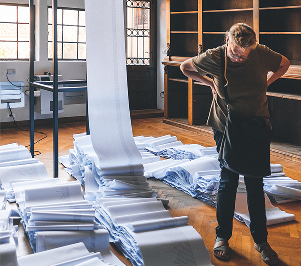 A male worker is looking at a stack of newly woven fabric in possibly a mill, the fabric is draped from the ceiling