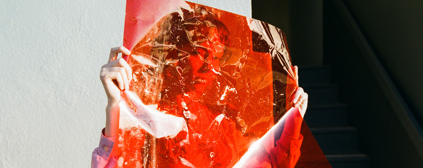 A woman is shown hiding behind a transparent red foil or film