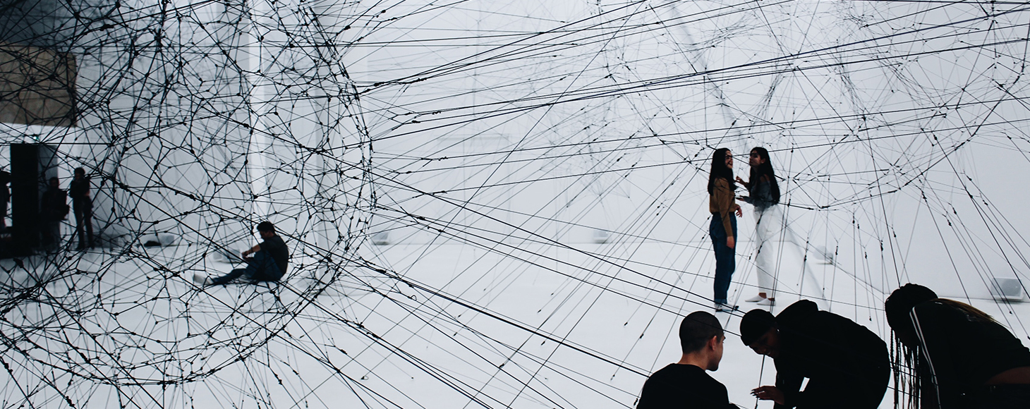 A gallery space is shown that has an artwork made of ropes in a round shape